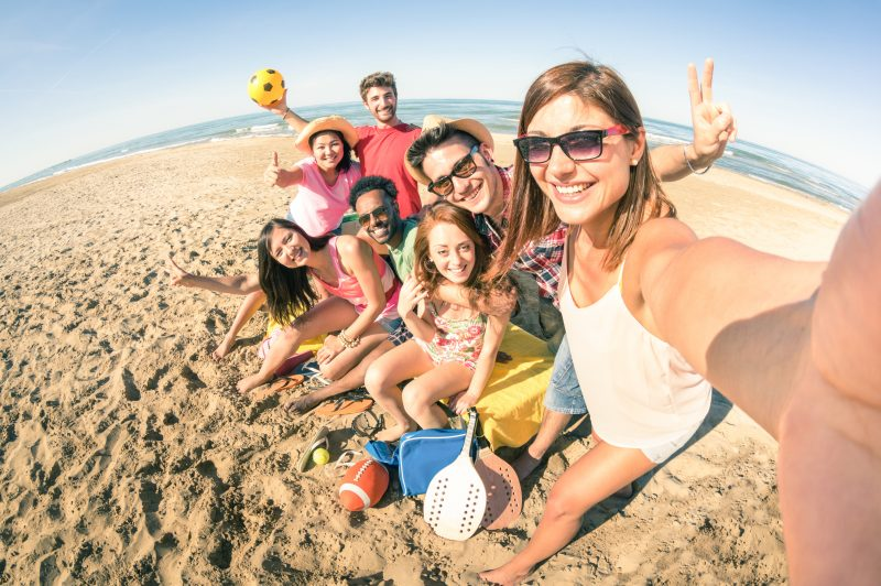 Group of multiracial happy friends taking selfie and having fun at beach - Friendship concept with summer sports equipment