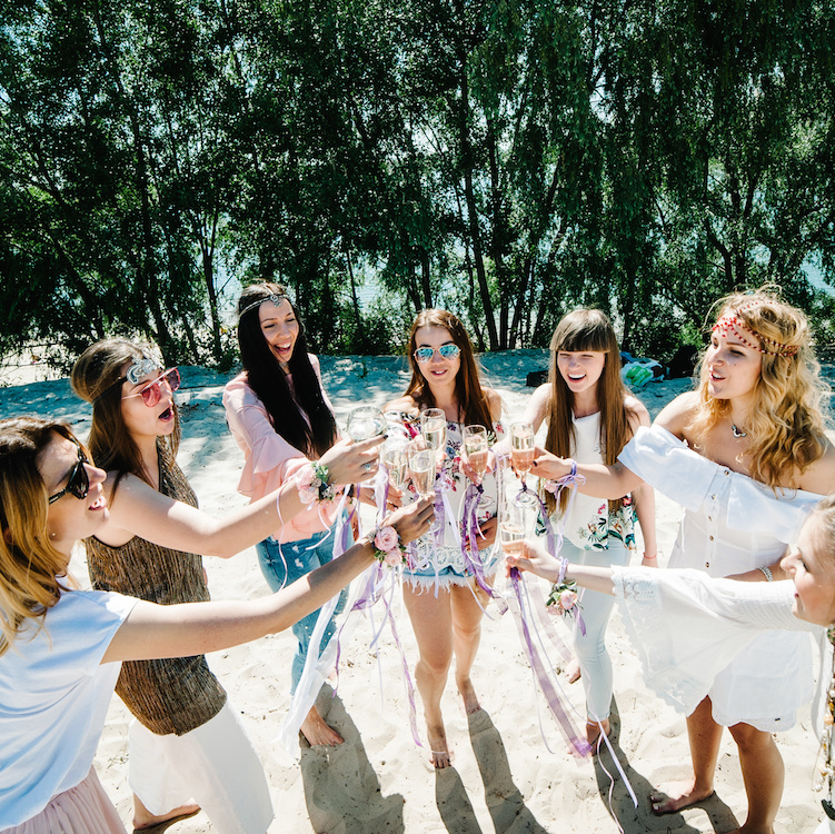 Beautiful happy stylish young girls on sand beach climb glass champagne. Glasses decorated with ribbons flowers. Party in Style boho. Maiden evening Hen-parties. Bachelorette. Close up. Place for text