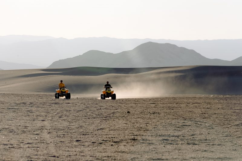 two-people-riding-atv-on-desert-2986409