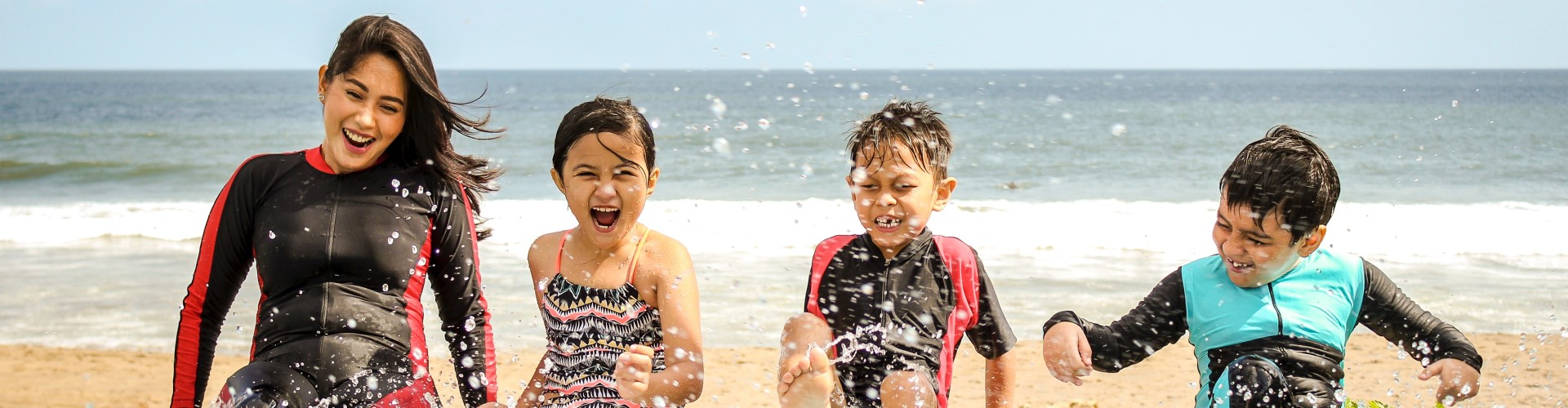 woman-and-three-children-playing-water-1231365